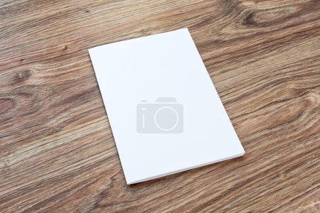 Photo pour Le blanc de la brochure se trouve sur un bureau en bois. Modèle pour votre conception . - image libre de droit