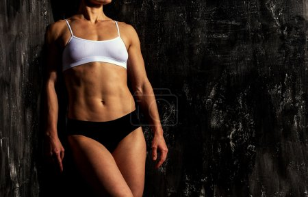 Muscular woman on a black background
