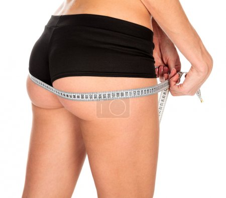 Slim woman measures her butt, isolated on a white background