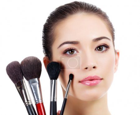 Pretty woman with a makeup brushes, isolated on white