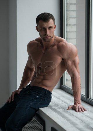 Photo pour Modèle masculin musclé à la fenêtre - image libre de droit