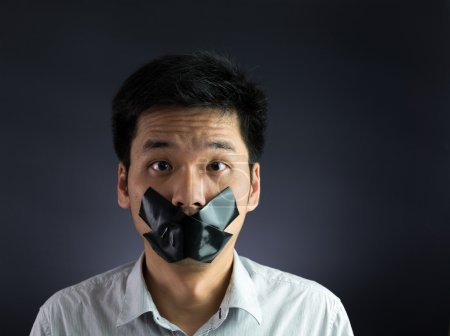Man with black tape over his mouth on black backgr...