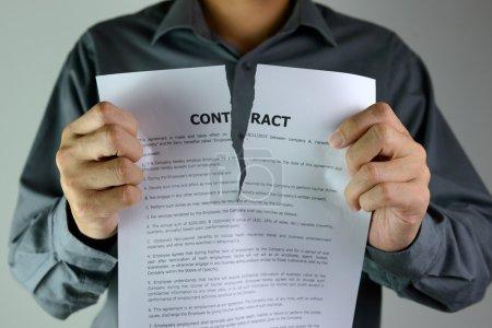Photo pour Un homme d'affaires déchire un contrat jusqu'au centre - image libre de droit
