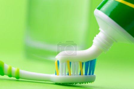 Photo pour Gros plan du dentifrice à presser sur la brosse à dents sur fond vert - image libre de droit