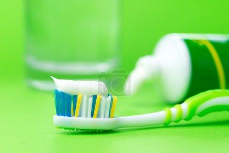Photo pour Gros plan de la brosse à dents et du tube de dentifrice sur fond vert - image libre de droit
