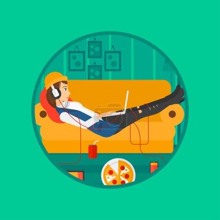 Frau liegt mit vielen Gadgets auf Sofa.