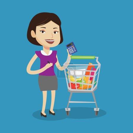 Illustration pour Jeune femme joyeuse debout près d'un chariot de supermarché rempli de produits et tenant une calculatrice à la main. Femme vérifiant les prix avec calculatrice. Illustration vectorielle de design plat. Aménagement carré . - image libre de droit