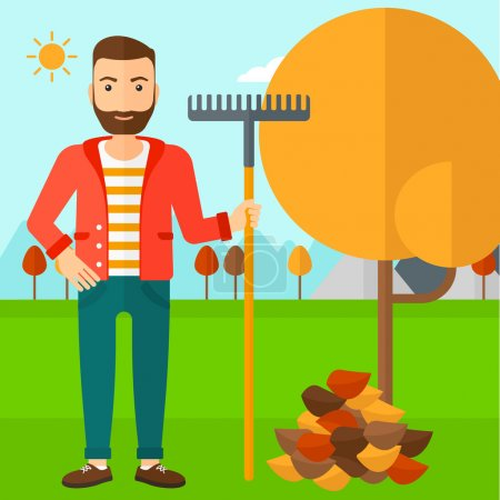 Man with rake standing near tree and heap of autumn leaves.