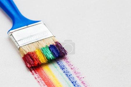 Pinsel und bunte Regenbogenpinselstriche auf weißem Künstler