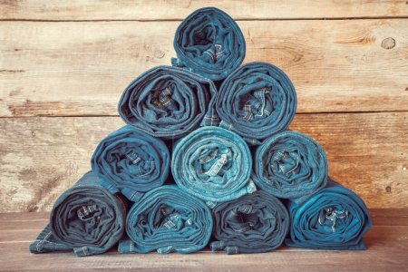 Rolled jeans stack on wooden background, retro toned.