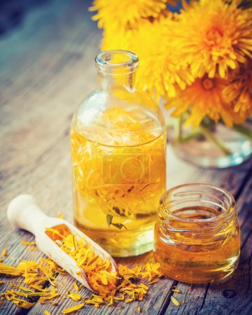 Bottle of dandelion tincture or oil, flower bunch and honey jar