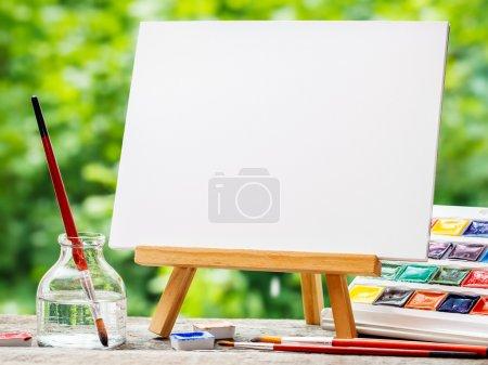Photo pour Carnet de croquis sur chevalet, aquarelle, pinceaux artistiques et bouteille d'eau sur table à l'extérieur . - image libre de droit