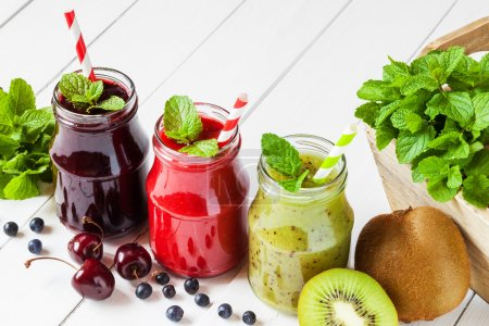 Photo for Healthy smoothie from summer fruits and berries in a jars with straws - Royalty Free Image