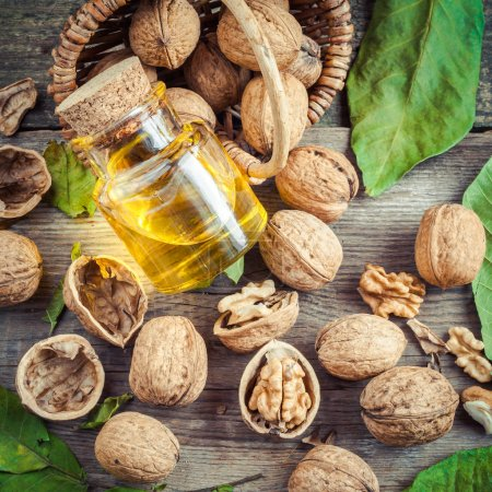 Walnuts, bottle of nut oil and basket on old table