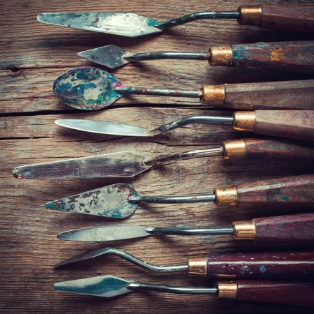 row of artist palette knifes on old wooden table