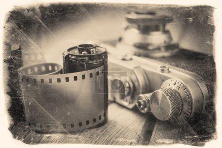 Foto de Old photo film roll and retro camera on desk. Vintage stylized photo. - Imagen libre de derechos