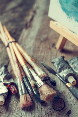 Foto de Artistic paintbrushes, tubes of oil paint, palette knife and easel with oil painting on old wooden desk. - Imagen libre de derechos