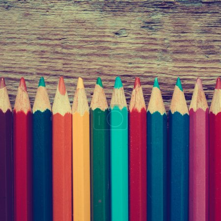 Row of colored drawing pencils closeup on old desk.
