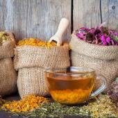 Léčivé byliny v tašky zkřížili a šálek zdravé čaje na rustikální dřevo