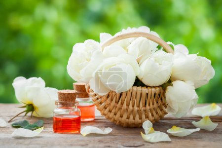 Wicker basket with roses bunch and bottles of essential oil.