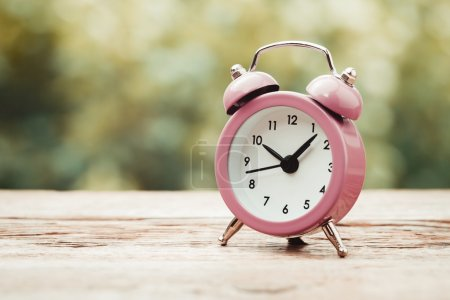 Vintage stylized photo of alarm clock on wooden table