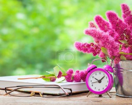 Photo pour Vintage nature morte : fleurs dans le seau, réveil rose et seau sur la table en bois à l'extérieur - image libre de droit