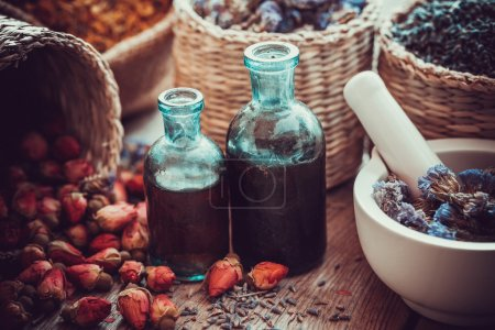 Bottles of tincture, basket with rose buds, and dried forget me