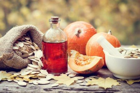 Pumpkin seeds oil bottle, pumpkins, bag with seeds and mortar