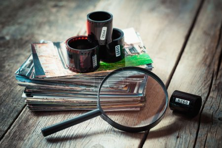 Photo film rolls, retro camera, stack of photos and magnifier