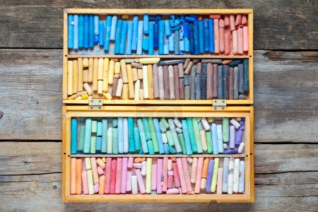 Multicolored art pastel crayons in open wooden artist box