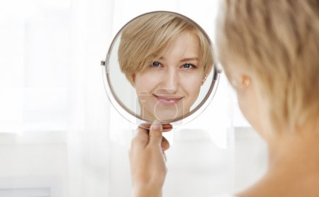 Beautiful healthy young woman looking in the mirror