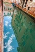 buildings reflected on water canal in Venice