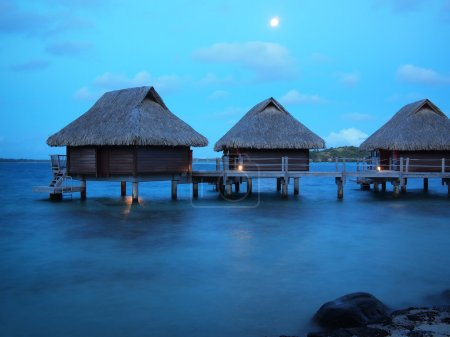 Thatched roof overwater bungalows at blue hour