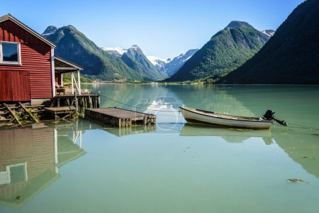 Photo pour Reflection of a boat, a jetty, a red boathouse and mountains in the tranquil water of Fjærlandsfjord, part of the Sognefjord in the village of Fjærland or Mundal, Sogn og Fjordane, Fjord Norway - image libre de droit
