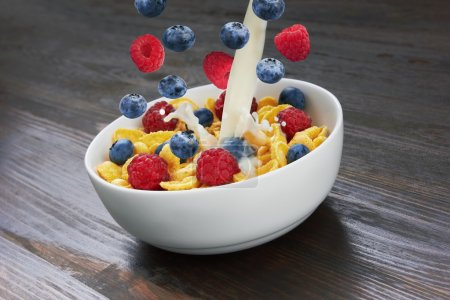 Photo for Falling corn flakes with fresh berries and pouring milk on wooden background - Royalty Free Image