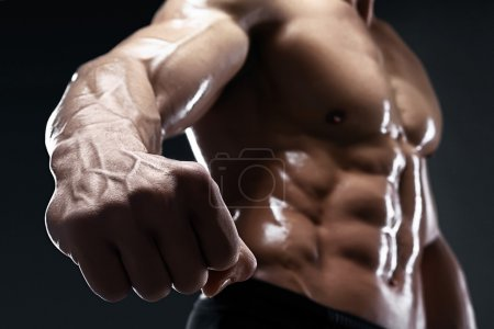 Handsome muscular bodybuilder shows his fist and vein.