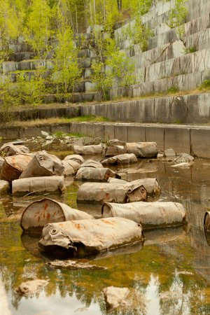 Old marble quarry, abandoned fuel barrels on bottom. Careless attitude towards nature. Industrial waste products of oil refining. Extraction of minerals by open method.