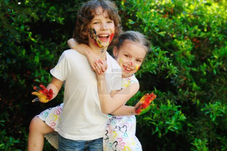 Photo for Children soiled with paint and show their dirty hands to the camera. Kids creativity. Baby art. Emotions. Children playing. Girl hugging a boy, their faces and hands in paint. - Royalty Free Image