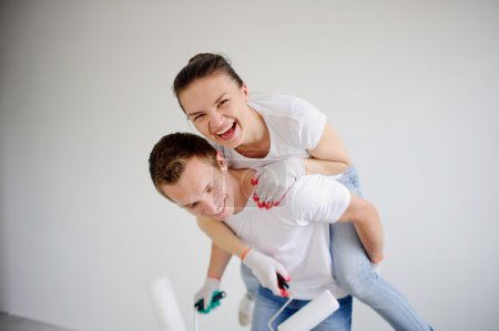 Foto de The guy and the girl have fun, doing repair in the house. The girl has got on a back to the guy. She laughs looking in a chamber. In hands at couple rollers. The young man looks down. - Imagen libre de derechos
