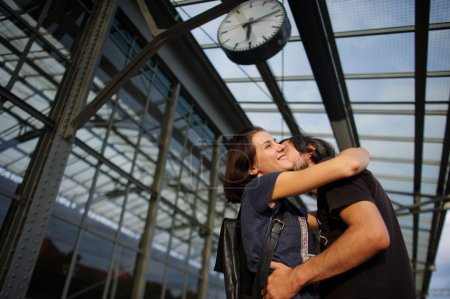 Photo pour Couple aimant rencontré ou séparé sur la plate-forme sous l'horloge. Le jeune homme mit son bras autour de la fille. Fille souriant joyeusement . - image libre de droit