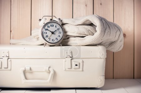 Foto de Beige knitted sweater, alarm clock and vintage suitcase on wooden background, retro decor - Imagen libre de derechos