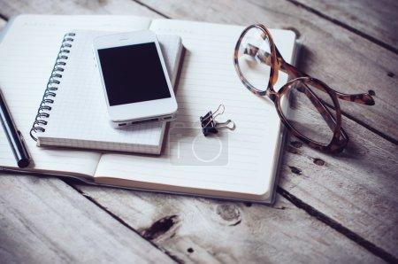 Photo pour Hipster bureau à domicile dessus de table : papiers et cahiers, lunettes de lecture, téléphone intelligent, stylo sur un vieux fond de planche en bois. Style de vie vintage - image libre de droit