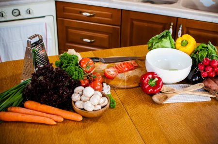 Photo for Fresh spring vegetables on the kitchen table. Homemade food preparation - Royalty Free Image