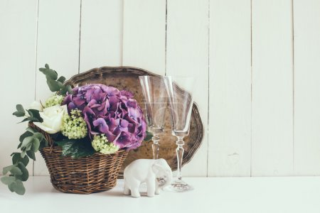 Foto de Big bouquet of fresh flowers, purple hydrangeas and white roses in a wicker basket, wine glasses and rustic wedding decor on a shelf in the interior, vintage style - Imagen libre de derechos
