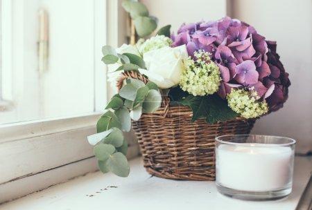 Foto de Big bouquet of fresh flowers, purple hydrangeas and white roses in a wicker basket on a windowsill, home decor, vintage style - Imagen libre de derechos