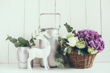 Photo for Big bouquet of fresh flowers, purple hydrangeas and white roses in a wicker basket and a rustic home decor on a shelf in the interior, vintage style - Royalty Free Image