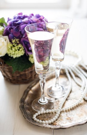 Foto de Big bouquet of fresh flowers, purple hydrangeas and white roses in a wicker basket, two glasses of champagne and vintage wedding decor with pearls on a table - Imagen libre de derechos