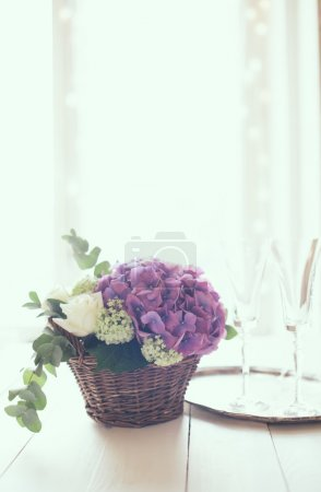 Foto de Big bouquet of fresh flowers, purple hydrangeas and white roses in a wicker basket, wine glasses and rustic wedding decor on a table in the interior, vintage style - Imagen libre de derechos