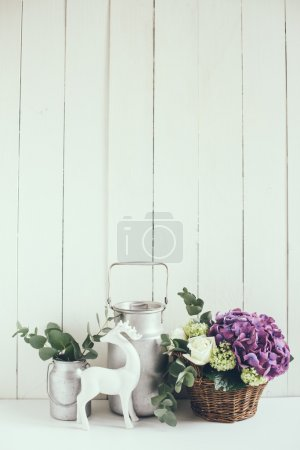 Foto de Big bouquet of fresh flowers, purple hydrangeas and white roses in a wicker basket and a rustic home decor on a shelf in the interior, vintage style - Imagen libre de derechos