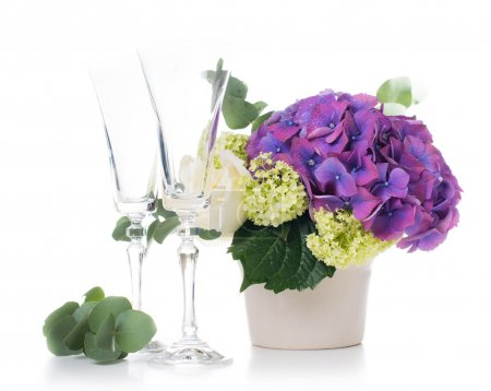 Foto de Big bouquet of fresh flowers, purple hydrangeas and white roses, and champagne glasses on a white background isolated - Imagen libre de derechos